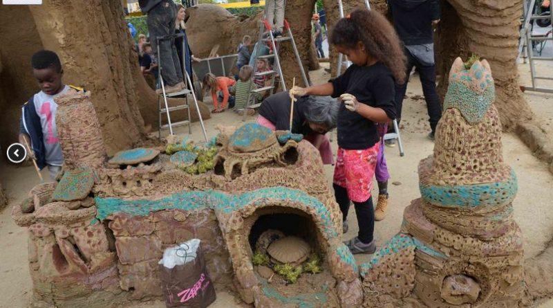 zwei Kinder erstellen Lehmskulpturen bei einer Bunte-Kuh-Aktion